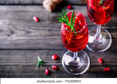 Pomegranate champagne mimosa cocktail with rosemary in glasses on wooden background