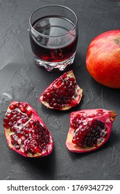 Pomegranate cuts with seeds in front of garnet cut and juice in glass side view, on black background, selective focus