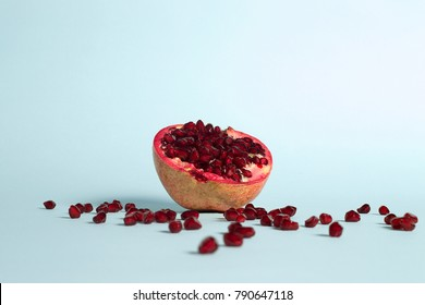 pomegranate fruit, cut, on a blue background