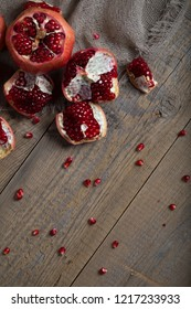 Pomegranate fruit on a wooden surface. Flat lay. Free space for a text
