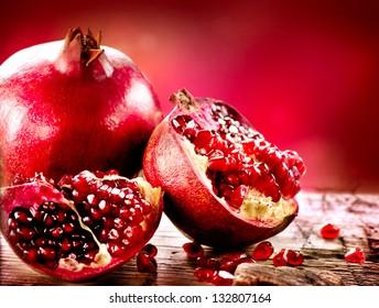 Pomegranate fruit. Pomegranates over Red Background. Organic Bio fruits