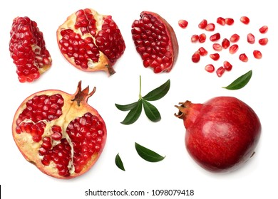 pomegranate fruit with seeds and green leaves isolated on white background top view
