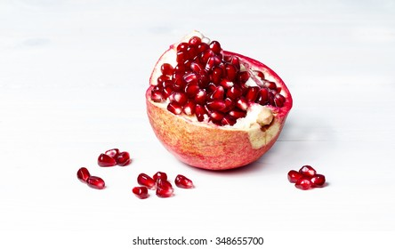 Pomegranate fruit, seeds, kiwi and leafs on white textured wooden board