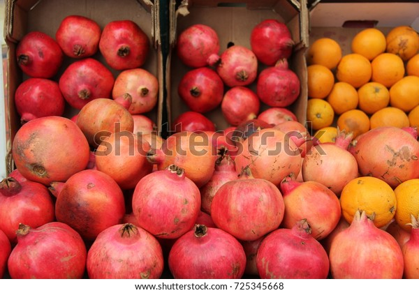 Pomegranate fruits stacked with oranges in the market stall