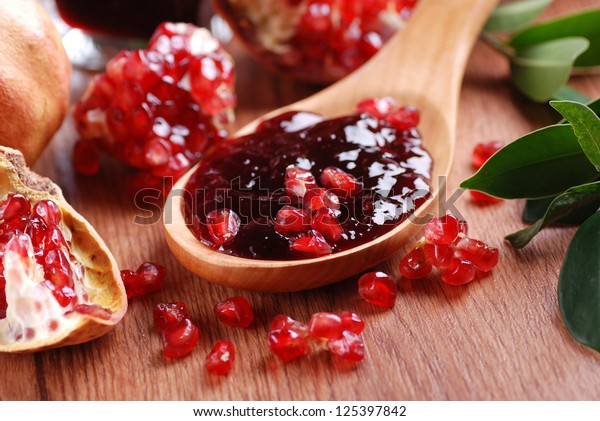 pomegranate jam in wooden spoon