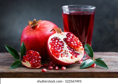 Pomegranate juice with pomegranate on a wooden board on a dark background