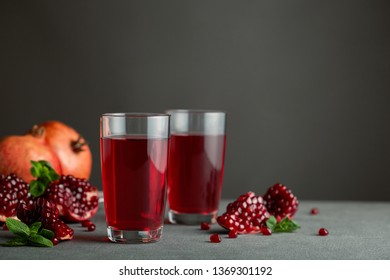 Pomegranate juice in a two glasses on gray background.
