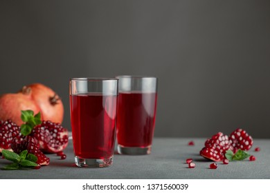 Pomegranate juice in two glasses on gray background.