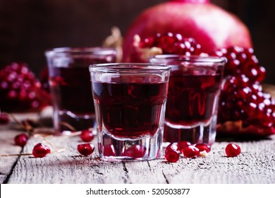 Pomegranate liqueur, old wooden background, selective focus