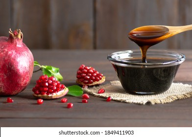 Pomegranate molasses in glass bowl, pomegranate sour sauce with fresh ripe whole and split pomegranate fruit on wooden rustic table (Punica granatum)
