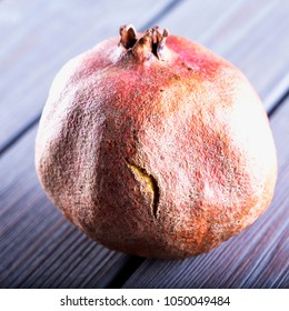 Pomegranate over wooden table, close up, square image