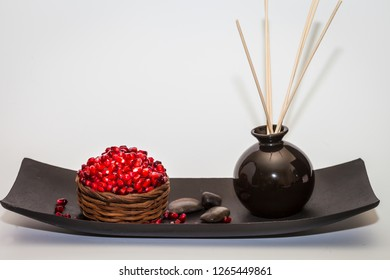 Pomegranate  red seeds displayed on a black plate. White background.  Studio Shot.  Stock Image.