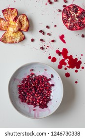 Pomegranate seeds in a blue bowl decorated by pomegranate juice and knife