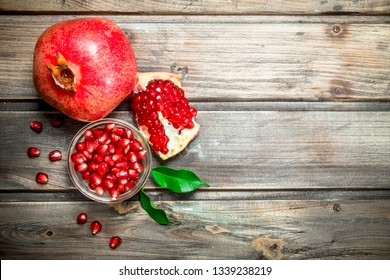 Pomegranate seeds in bowl and juicy pomegranate with leaves. On wooden background