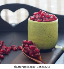 Pomegranate seeds  portion in green pottery. Valentines day concept