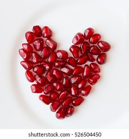 Pomegranate seeds in a shape of a heart isolated on white