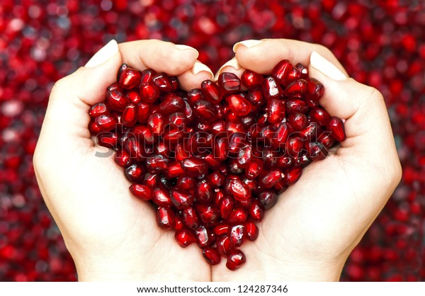 Pomegranate seeds in woman hands shaping heart symbol