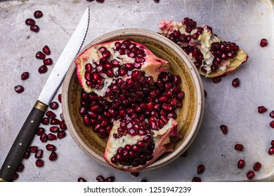 Pomegranate slices and seeds in a ceramic bowl. The fruits are on a metal background, and there are also some pomegranate seeds next to the bowl. From above flay lay perspective.