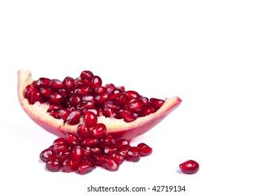 Pomegranate spilling over onto a white background