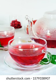 Pomegranate tea in glass tea cups and tea pot with mint leaves over white background, vertical