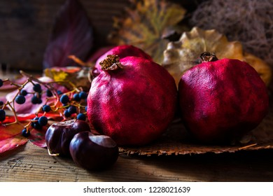 Pomegranates, decorative pumpkin  and horse chestnut on wooden table
