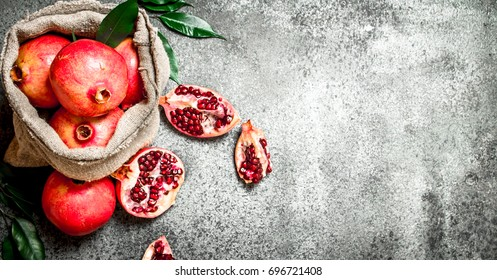 Pomegranates in the old bag. On rustic background.