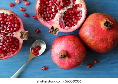 Pomegranates with spoon / blue background / sliced