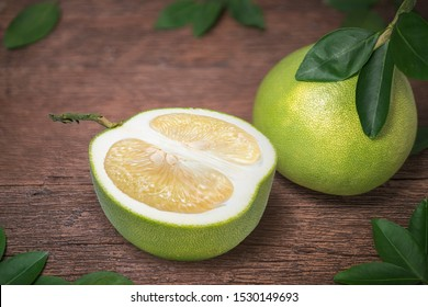 Pomelo fruit with leaves on the old wooden table.Whole pomelo with slice on wooden Background