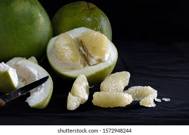 Pomelo fruit on dark background and black cloth floor / Select focus and still life image, space for text