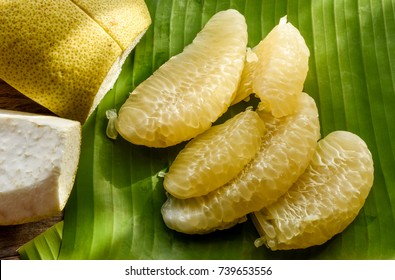 Pomelo or grapefruit. Fresh and tasty tropical fruit, pomelo or citrus grandis, peeled on banana leaf background.