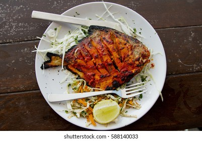Pomfret fish cooked in a clay oven (tandoor) garnished with lemon on a white plate and a brown wooden table in north Goa's Baga beach
