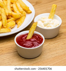 Pommes fries with sauces on wooden background