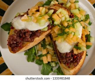 Pomodoro Pork Belly Bruschetta with mozzarella di bufala topped with a fruit salsa on a bed of arugula