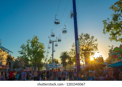 Pomona, California USA - September 23rd, 2018. Many people come to LA County fair. The street is filled with crowd of enjoying people. People in cable car can see top view and sunset sky.