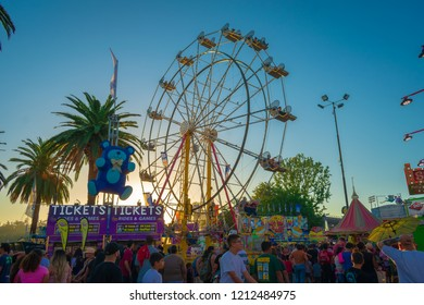 Pomona, California USA - September 23rd, 2018. many people walking in LA County fair with Ferris wheels against sunset blue sky background.