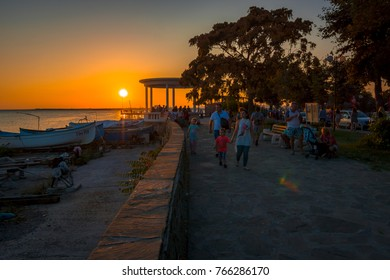 POMORIE, BULGARIA - AUGUST 26, 2017: Promenade with tourists and fishing boats on the shore of the seaport of the seaside resort town of Pomorie.
