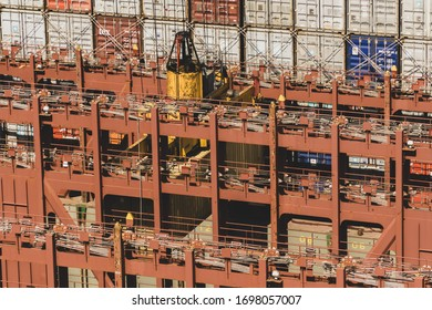 Gdańsk, Pomorskie / Poland: 10.06.2019: Drone photo of terminal crane STS loading container on one of the largest container ships in the world. Stacked Maersk containers in the backgroud.