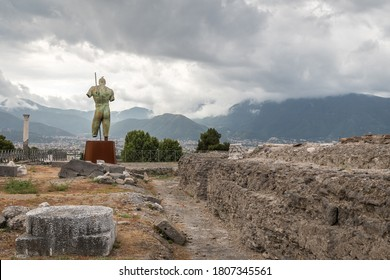 Pompei, Italy, Aug, 21 2020 -Pompeii ruins with the bronze sculpture by Igor Mitoraj - Daedalus, donated to Pompeii. In the distance-mountains and cloudy sky