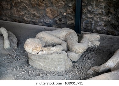 "Pompeii, Italy - April 17, 2018. Plaster cast of Pompeii victim, at the ""Garden of the fugitives"". Pompeii was an ancient Roman city which was destroyed by mount Vesuvius volcanic eruption in AD 79."