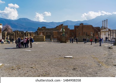 Pompeii, Italy February 09 2019: Foro di Pompeii with Statue of Centaur & tourists. Ancient Roman city archaeological site forum with visitors among ruins & modern bronze statue of centaur - Centauro.