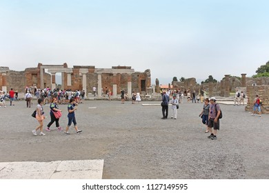 POMPEII, ITALY - June 25, 2014: Famous UNESCO heritage antique ruins in Pompeii. Large square with remains of destroyed ancient city Pompeii with tourists walking around observing the site.