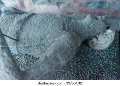 POMPEII, ITALY - November 29, 2014:Cast Body of man victim preserved in plaster cast who died in AD 79 Mount Vesuvius Volcano eruption. Close up of head and torso with part of skull and teeth exposed.