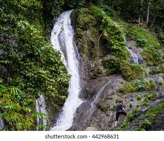 POMPONAN VILLAGE, THE PHILIPPINES - December 6, 2015: An American backpacker hikes near a waterfall outside Pomponan Village, Leyte Province, the Philippines on December 6, 2015.