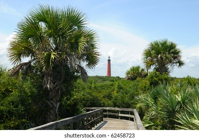 Ponce Lighthouse with lush, green foliage as seen from the hiking path and boardwalk at New Smyrna Beach, Florida.