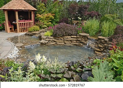 The pond area in the Reflections aquatic garden with planted rockery and outdoor eating