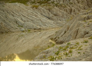 a pond bank which is white sand eroded by rainwater