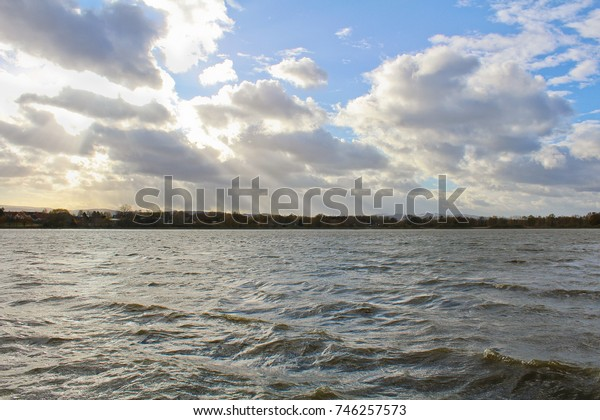 Pond with big wave in strong wind. Czech landscape