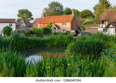 The pond and cottages bathed in evening sun light in Oakley hampshire