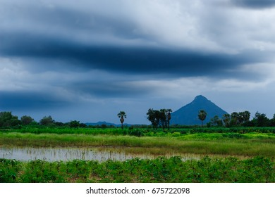 pond in farmland with mountain view and rainy cloud