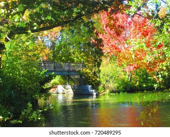 Pond with a footbridge hidden in the colorful Autumn leaves at a park in New England.